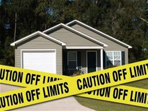 Caution off limit yellow tape in front of house